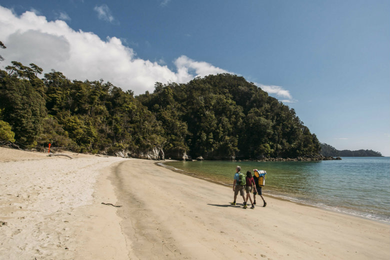 Walking on one of Abel Tasman's golden sand beaches