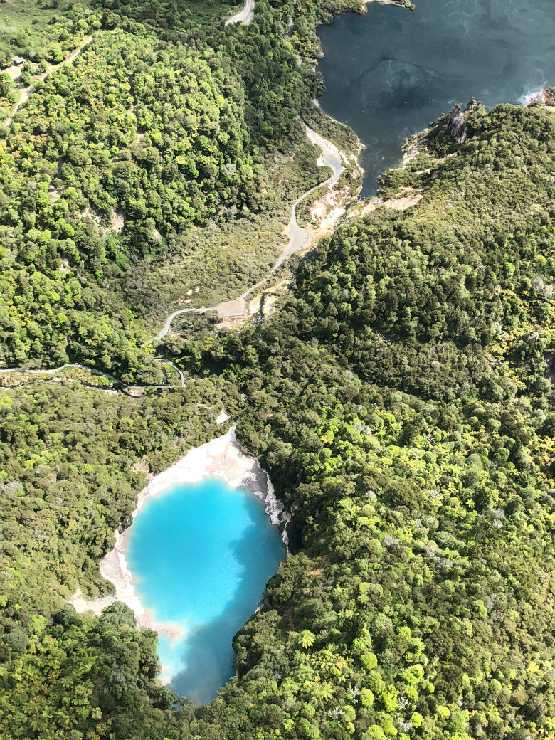 Flying over the geothermal blue lake in Waimangu Valley, Rotorua, New Zealand